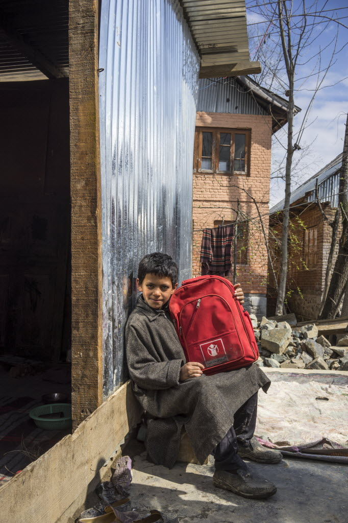 Here a young boy proudly holds up a relief kit from Save the Children in front of his temporary shelter in a village in India after severe flooding ruined his home.